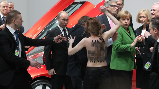 "PHOTO: Russian President Vladimir Putin is attacked by an activist of the Ukrainian women rights group Femen as German Chancellor Angela Merkel looks on during their visit of the industrial exhibition ""Hannover Messe,"" April 8, 2013, in Hannover, German"