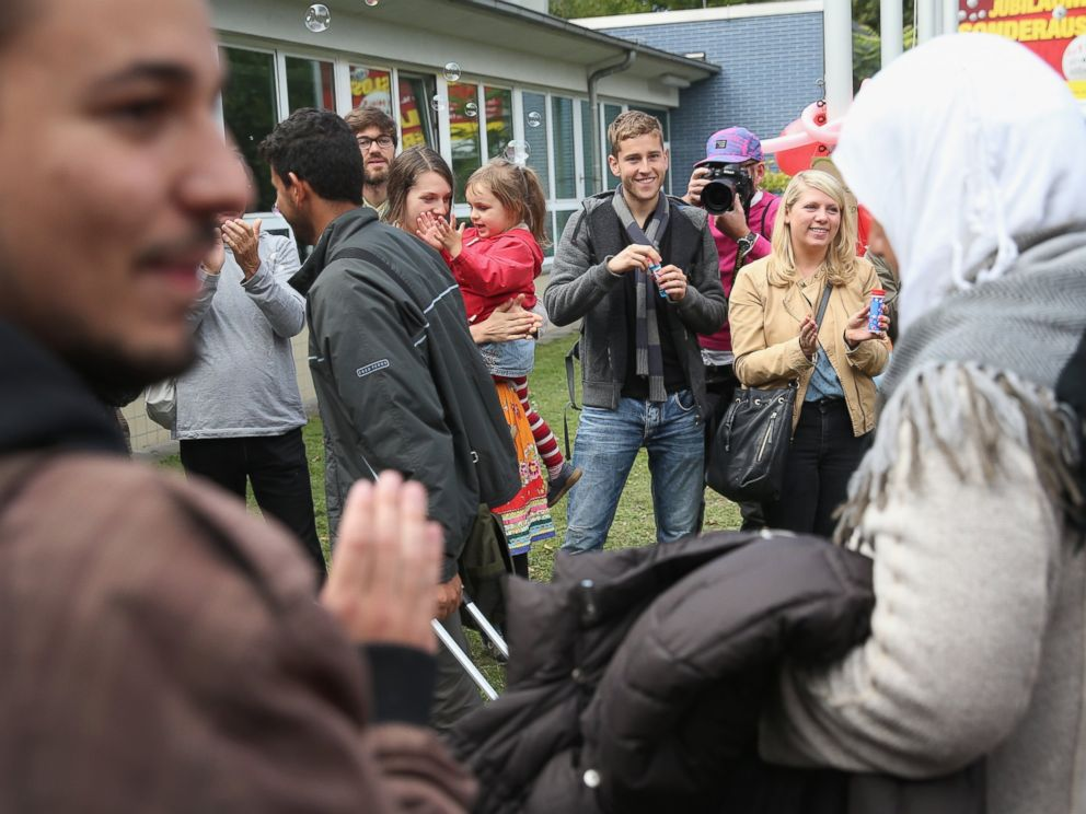 PHOTO: Refugees who arrived by train are greeted by locals welcoming them with soap bubbles and balloons at the Jahn-Sporthalle gymnasium in Berlin, Sept. 8, 2015.