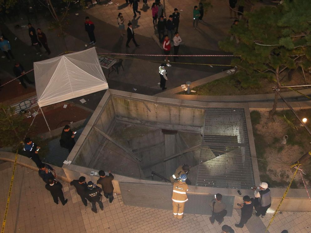 PHOTO: Rescue workers stand around a collapsed ventilation grate on Oct. 17, 2014 in Seongnam, South Korea.