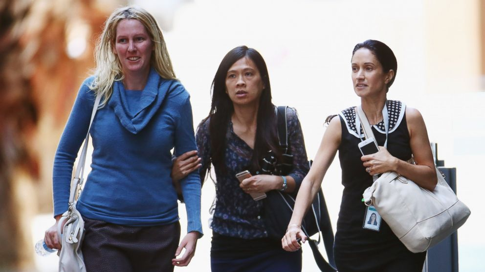 Girls rush through Philip Street past armed police at a cafe on Dec. 15, 2014 in Sydney, Australia.