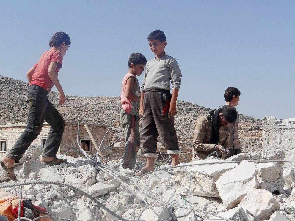 PHOTO: Syrian children collect items from the rubble of a destroyed house following the U.S.-led coalitions airstrikes in Idlib, Syria on Sept. 23, 2014.