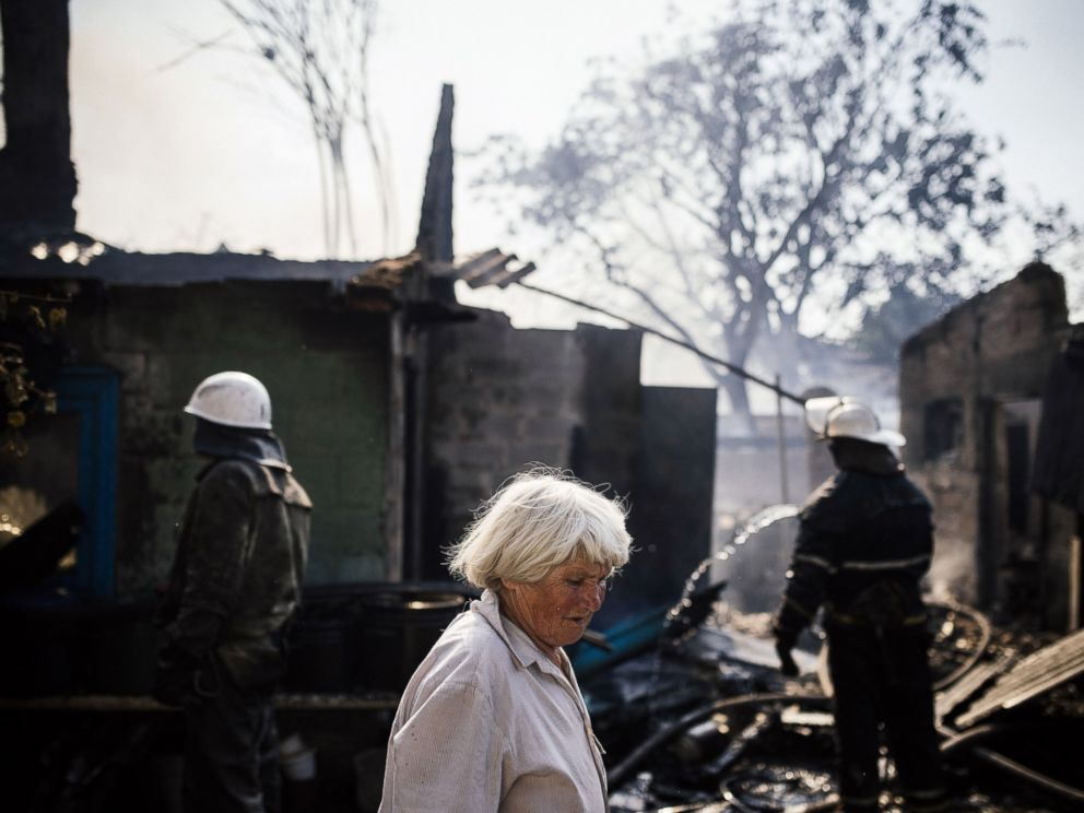 PHOTO: A woman walks past firemen and burnt houses after shelling in Donetsk, Aug. 16, 2014.