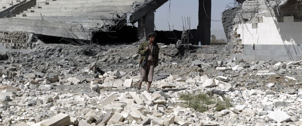 PHOTO: A Shiite Huthi rebel walks above debris on April 12, 2015 at the compound of Sanaas al-Yarmuk football club which was reported hit by an air strike by the Saudi-led coalition the previous day in the Yemeni capitals northern al-Rawda district.