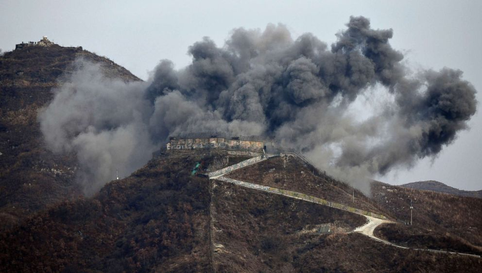 PHOTO: Smoke and debris from an explosion rises as part of the dismantling of a South Korean guard post, Nov. 15, 2018, in the Demilitarized Zone dividing the two Koreas in Cheorwon, as a North Korean guard post sits high in the upper left.
