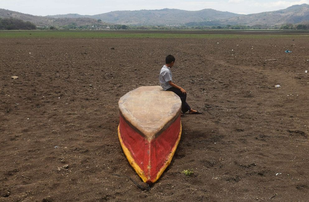 PHOTO: A boy sits on an abandoned boat on what is left of Lake Atescatempa, which has dried up due to drought and high temperatures, in Atescatempa, Guatemala, on May 5, 2017.
