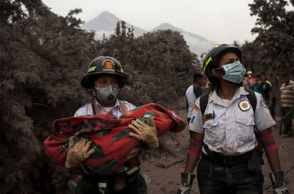 PHOTO: A firefighter carries the body of a child recovered near the Volcan de Fuego, or Volcano of Fire, in Escuintla, Guatemala, June 4, 2018.