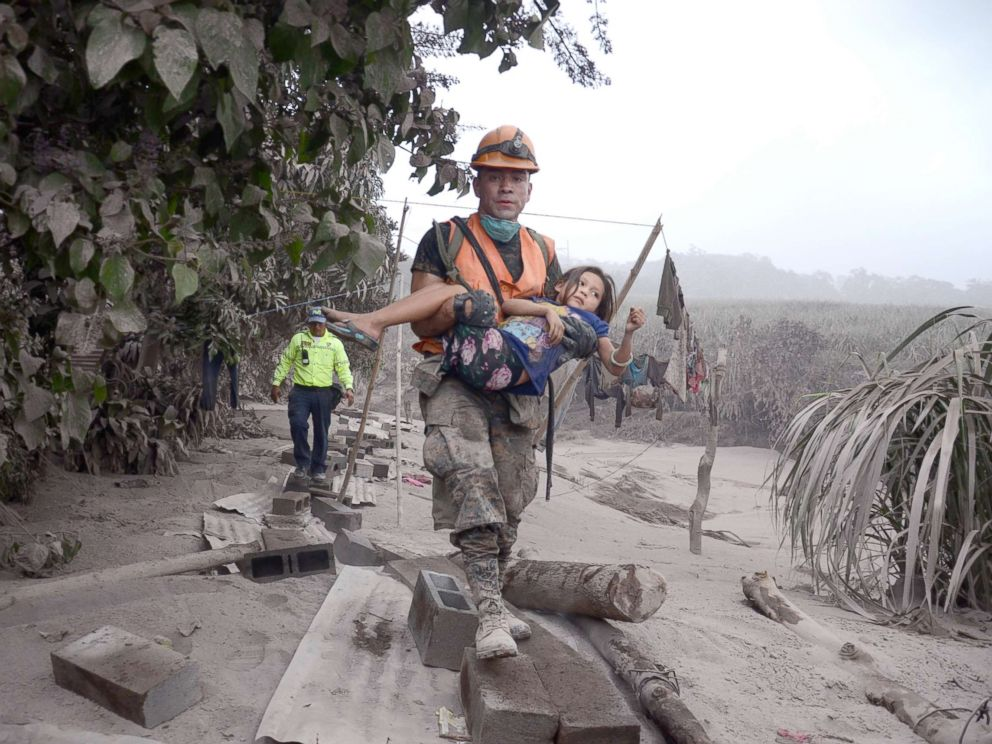 PHOTO: A Guatemalan rescue team worker carries a girl in El Rodeo, Escuintla, Guatemala, June 3, 2018, after the eruption at Fuego volcano, which has left at least 25 dead, around 20 injured and more than 1.7 million people were affected.