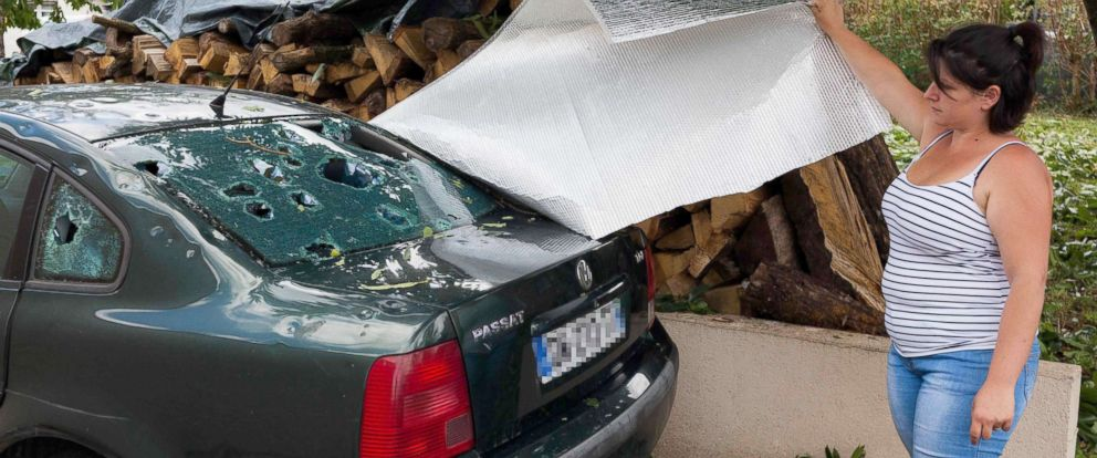 PHOTO: A woman shows the rear window of a damaged vehicle in the village of Saint-Sornin, July 5, 2018, after violent hailstorms ripped through the area some 50 miles north-west of Bordeaux in western France late July 4.