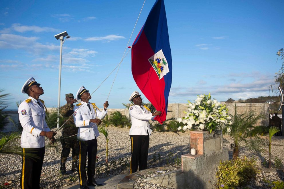 National police officers raise a Haitian national flag during a memorial service honoring the victims of the 2010 earthquake, at Titanyen, a mass burial site north of Port-au-Prince, Haiti, Jan. 12, 2018.