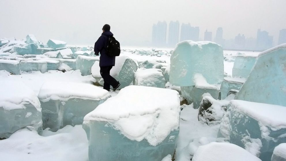 PHOTO: Bob Woodruff walks by blocks of ice along the Songhua River in China.