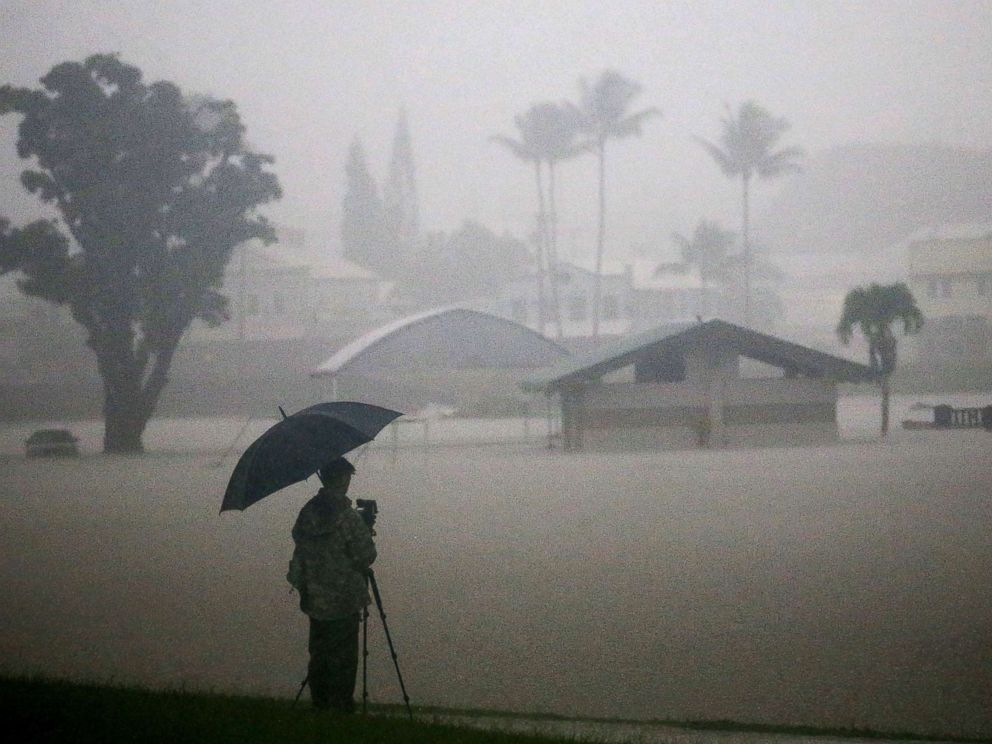 PHOTO: A man takes photos of floodwaters from Hurricane Lane rainfall on the Big Island, Aug. 23, 2018, in Hilo, Hawaii. Hurricane Lane has brought more than a foot of rain to some parts of the Big Island which is under a flash flood warning.