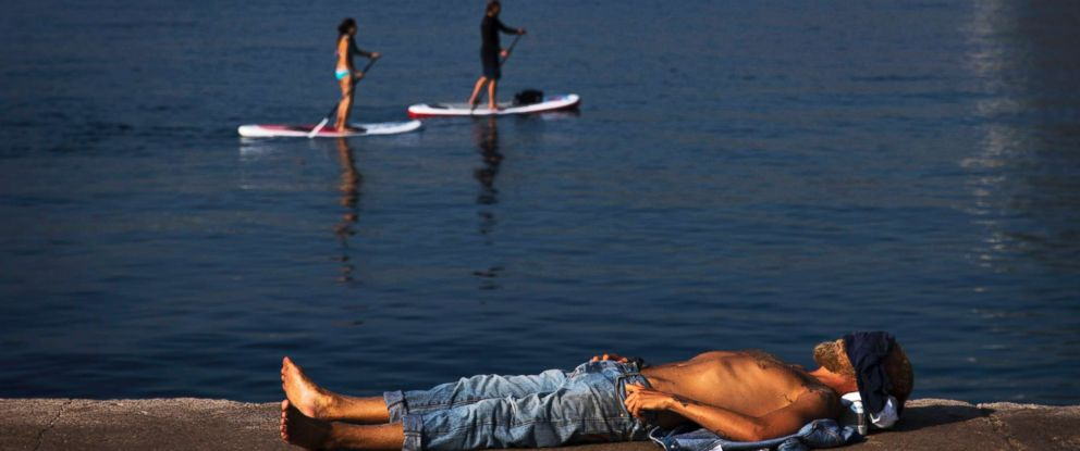PHOTO: A man rests next to the beach during a hot summer day in Barcelona, Aug. 3, 2018.