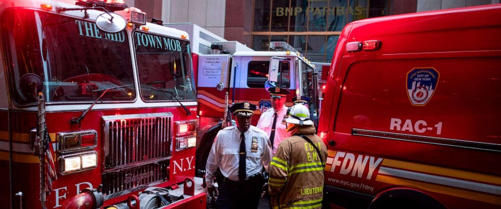 PHOTO: Police officers and Firemen talk after a helicopter crash-landed on top of a building in New York, June 10, 2019.