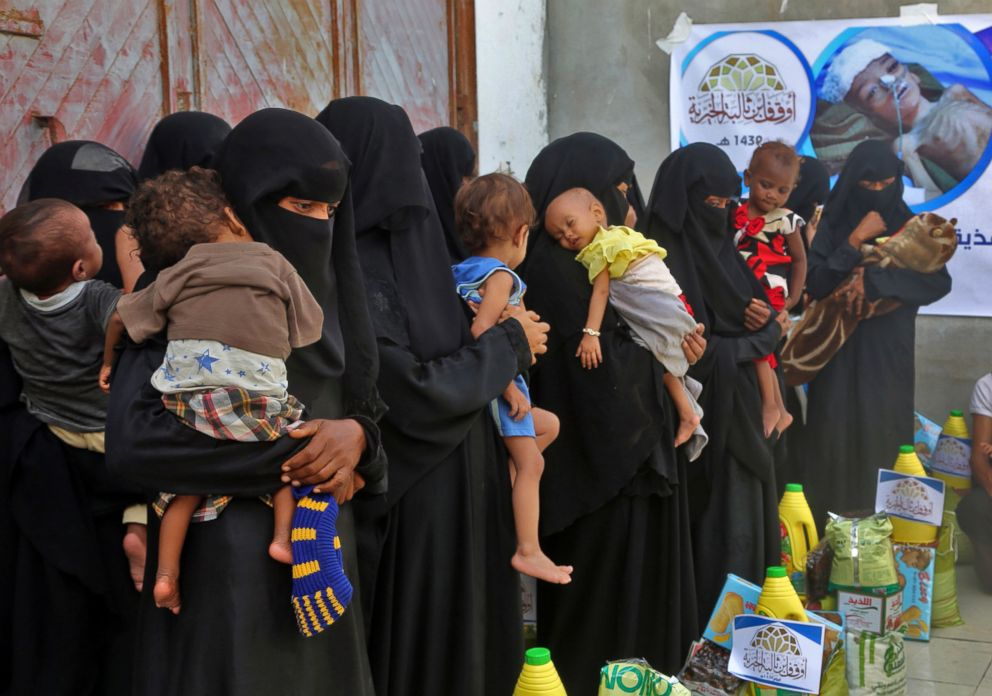 PHOTO: Yemeni women and children wait during food distribution in Hodeida, Yemen, May 30, 2018.