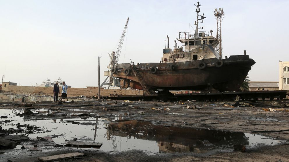 Workers inspect damages at the site of an air strike on the maintenance hub at the Hodeidah port, May 27, 2018.
