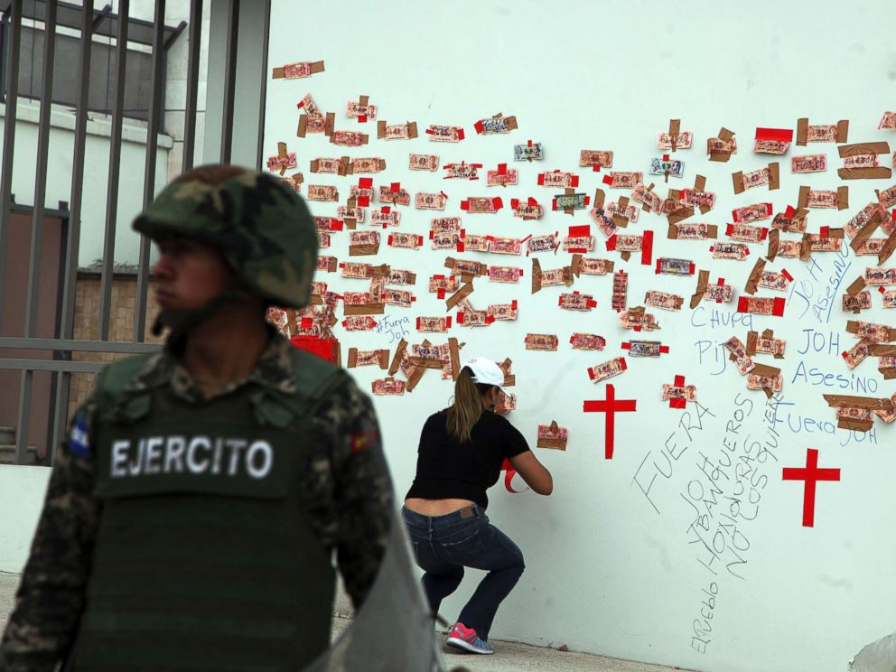 PHOTO: A protester tapes Honduran money inscribed with political slogans alongside crosses representing people killed in post-election violence, on the outside of the central bank in Tegucigalpa, Honduras, Jan. 7, 2018.