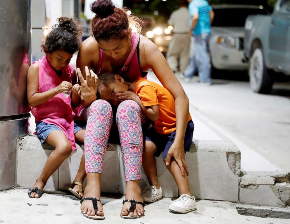 PHOTO: Fransisca Sislavas sits next to her daughter Brittany and her son Rony near the vehicle after an unidentified gunman killed her husband in a taxi in San Pedro Sula, Honduras, July 26, 2018.