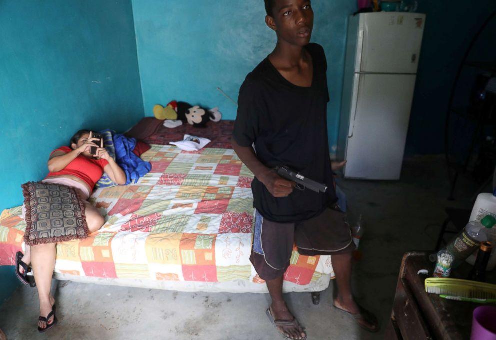 PHOTO: A Barrio-18 gang member holds a gun in a house in San Pedro Sula, Honduras, Sept. 20, 2018.