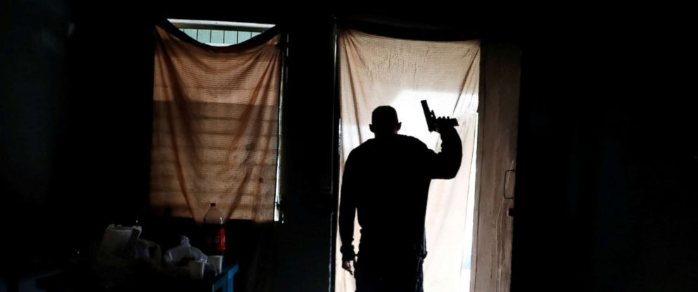 PHOTO: A member of MS-13 street gang looks out from a house as police patrol the street outside, in San Pedro Sula, Honduras Sept. 29, 2018.