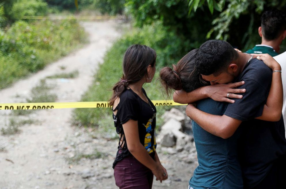 PHOTO: The friends of two men who were killed in gang violence cry at the crime scene in San Pedro Sula, Honduras, July 24, 2018.