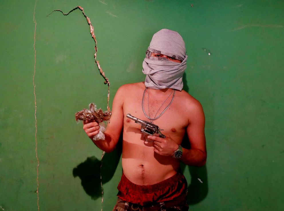 PHOTO: An MS-13 gang member poses for a photograph as he holds a gun and a bag of marijuana in San Pedro Sula, Honduras, Oct 6, 2018. The gang member described himself as a drug dealer and assassin.
