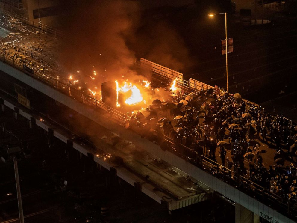 PHOTO: A police vehicle is set on fire as demonstrators throw fire bombs on a bridge at The Hong Kong Polytechnic University, Nov. 17, 2019, in Hong Kong.