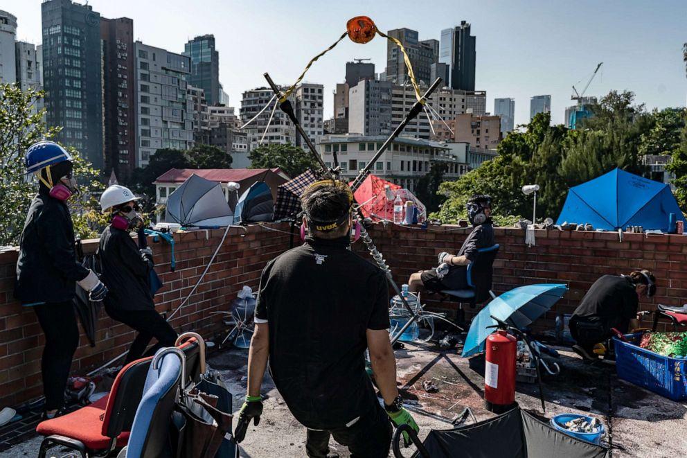 PHOTO: Demonstrators use a catapult to fire a brick at the Hong Kong Polytechnic University, Nov. 17, 2019, in Hong Kong.