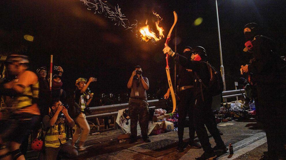 Hong Kong Demonstranten, bewaffnet mit Bögen und Pfeilen ducken an Universitäten