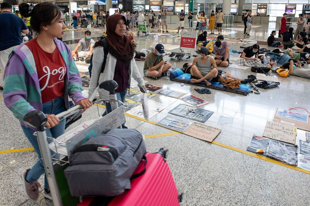 PHOTO: Passengers walk past anti-government protesters as they continue their sit-in at a designated protest area at Hong Kong Chek Lap Kok International Airport, in Hong Kong, China, August 14, 2019.