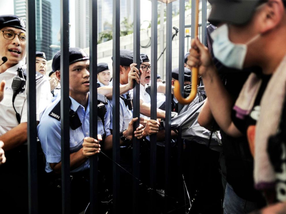 PHOTO: Police officers hold on to the gate as they block and argue with protesters who surrounded the police headquarters in Hong Kong, June 21, 2019.