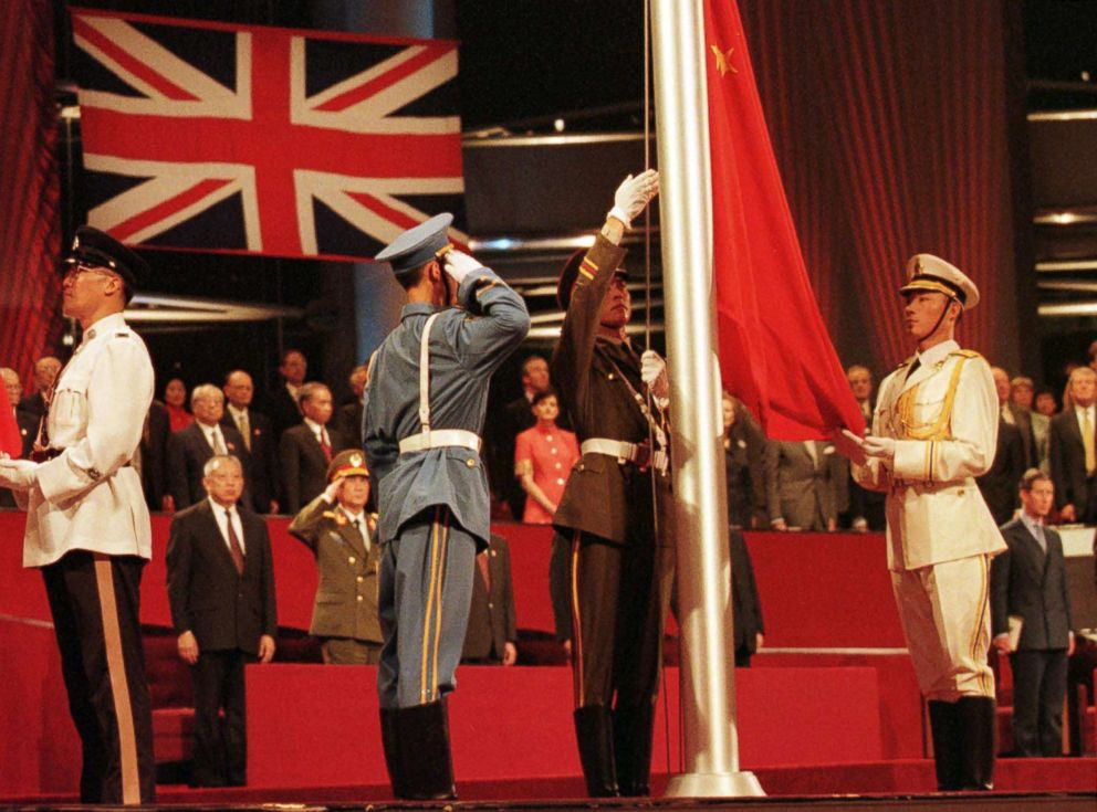 PHOTO: Members of the combined Chinese Armed Forces raise the Chinese Flag at the Hong Kong convention center on July 1, 1997 marking the moment Hong Kong reverted to Chinese rule.