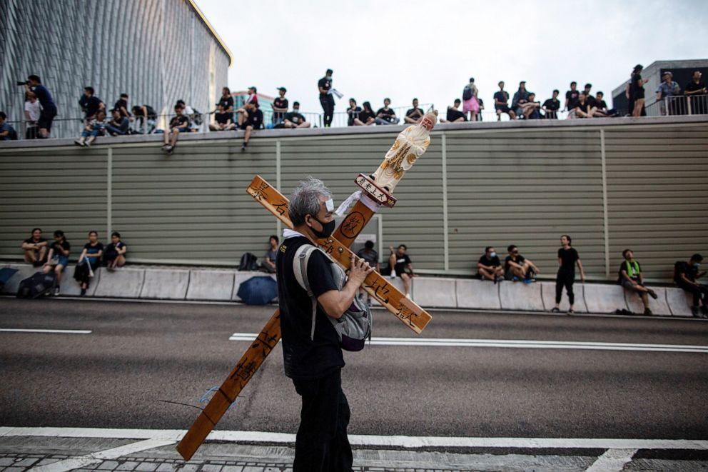 PHOTO: A man carries a cross as anti-extradition bill protesters gather on a road near West Kowloon railway station during a march in Hong Kong, China, July 07, 2019.