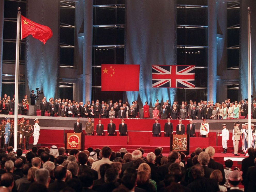PHOTO: Officials participate in the handover ceremony, July 1, 1997, after the Chinese flag was raided (left) and the Union Jack was lowered.