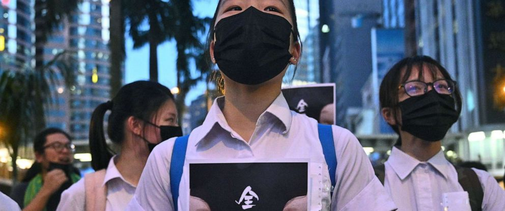 """PHOTO: TOPSHOT - High school students chant slogans as they stick posters reading """"all people masked"""" on their uniforms as protesters gather in Hong Kong, Oct. 4, 2019, after the government announced a ban on face masks."""