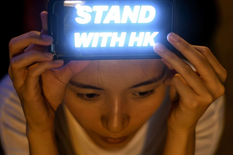 PHOTO: A pro-democracy protester holds a luminous sign as she attends a rally in Hong Kong on August 16, 2019.