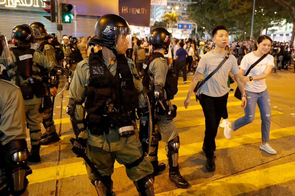 PHOTO: Residents past by police in riot gear during street protests in Hong Kong on Saturday, Aug. 10, 2019.