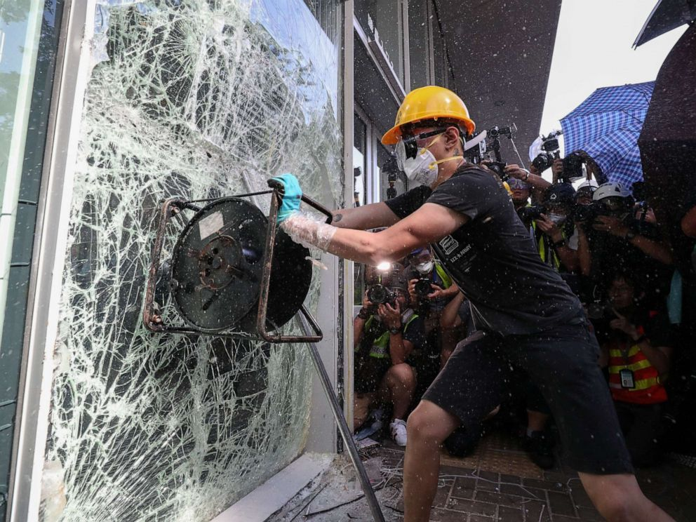 PHOTO: A protester breaks a window of the Legislative Council in Hong Kong, July 1, 2019.