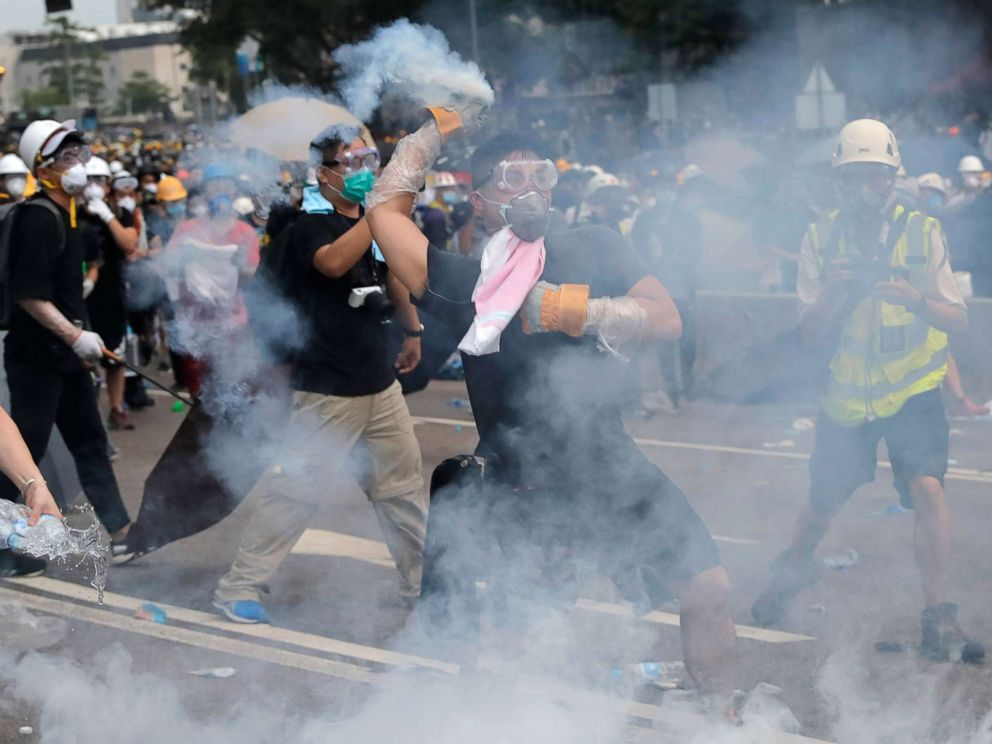 PHOTO:A demonstrator throws a canister of tear gas back towards the police outside the Legislative Council in Hong Kong, June 12, 2019.