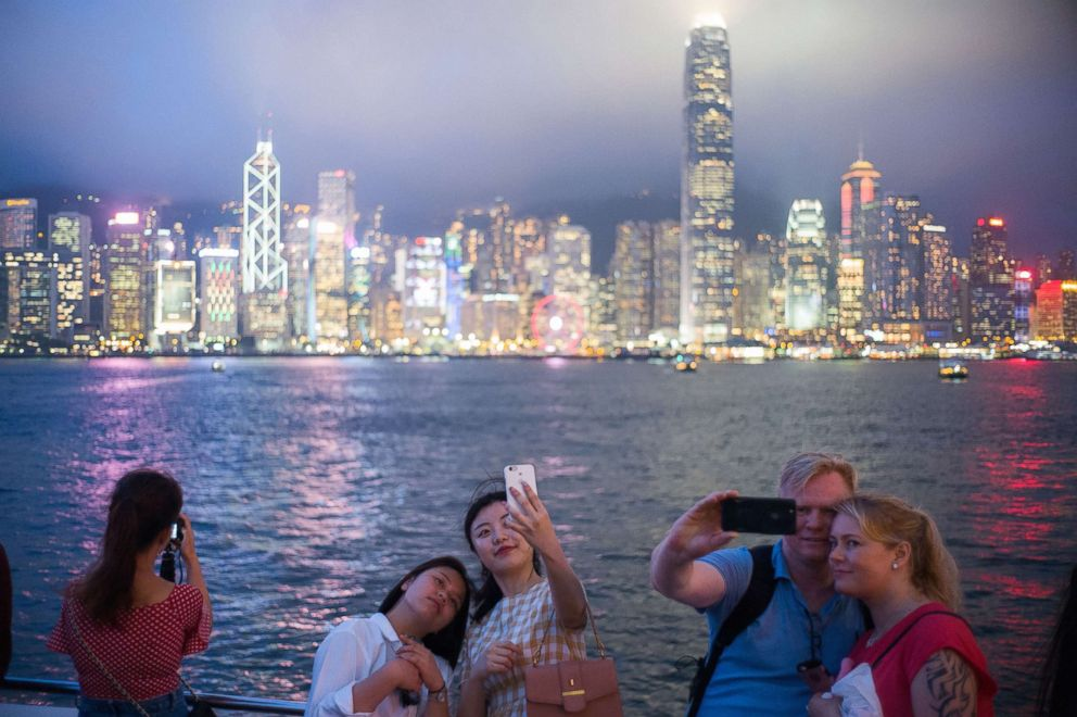 PHOTO: Tourists pose for selfies in front of a view of Victoria Harbour and the skyline of Hong Kong, May 7, 2018.
