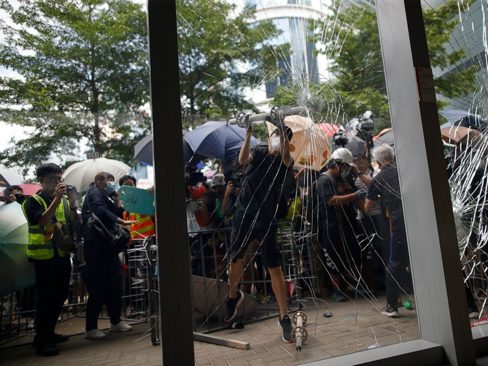 PHOTO: A protester tries to break the glass to get into the Legislative Council in Hong Kong Monday, July 1, 2019.