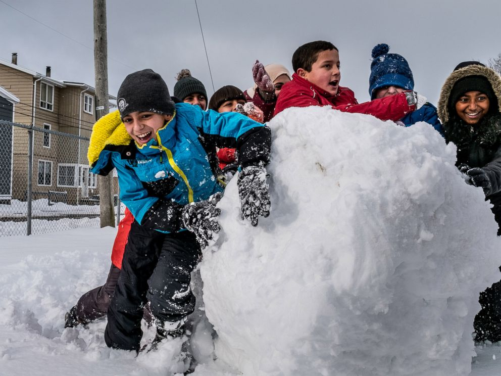 PHOTO: Basel Alrashdan, 11, plays with other sixth graders in the snow at St. Jean Elementary School in Charlottetown on Prince Edward Island, Canada, on Dec. 13, 2016.
