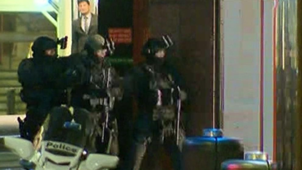 Armed police enter a cafe where hostages are being held at Martin Place in the central business district of Sydney, Australia, Dec. 15, 2014.