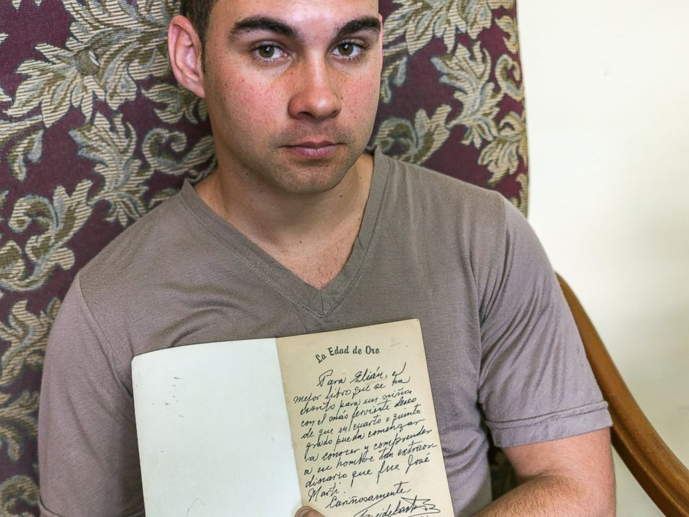 PHOTO: Elian Gonzalez holds a copy of La Edad de Oro by Jose Marti, given to him and signed by Fidel Castro, July 2000.