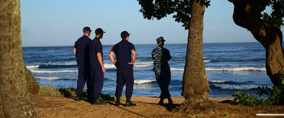 PHOTO: Coast Guardsmen and a Navy sailor scan the shoreline outside the Haleiwa Incident Command Post in Haleiwa, Hawaii, Jan. 18, 2016.