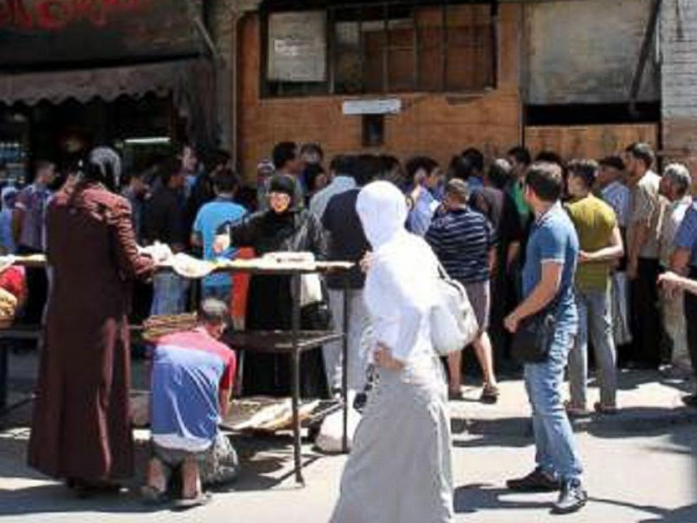 PHOTO: Long lines are typical outside Syrian bakeries. Some customers are turning to middlemen to avoid the wait.