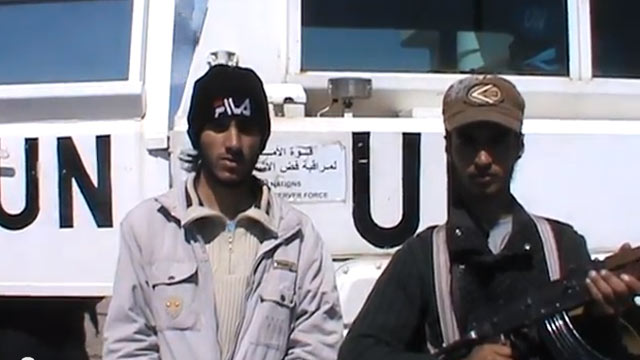 "PHOTO: In this image from video published March 6, 2013, a man who claims to be a member of the ""Martyrs Brigade of Yarmouk"" says the convoy will not be released until forces loyal to Assad withdrew from the village of Jamla, a mile east of the ceasefire"