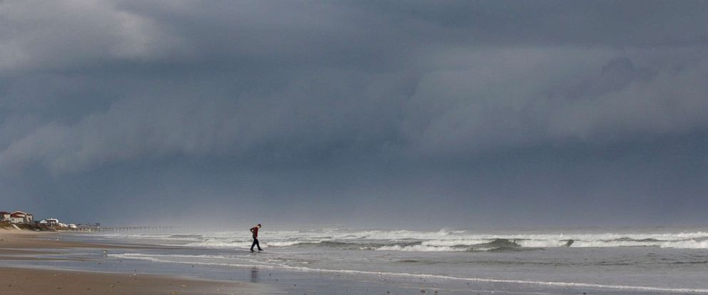 PHOTO: A storm front looms behind Seth Loconte as he walks on the beach in North Topsail Beach, N.C., prior to Hurricane Florence moving toward the east coast on Sept. 12, 2018.