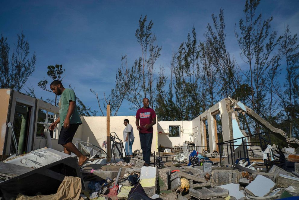 PHOTO: George Bolter, left, and his parents walk through the remains of his home destroyed by Hurricane Dorian in the Pine Bay neighborhood of Freeport, Bahamas, Wednesday, Sept. 4, 2019.