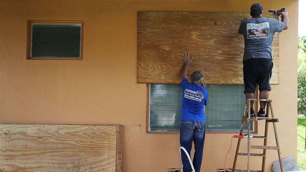 People put up shutters as they prepare a family member's house for Hurricane Irma, Sept. 6, 2017, in Miami.