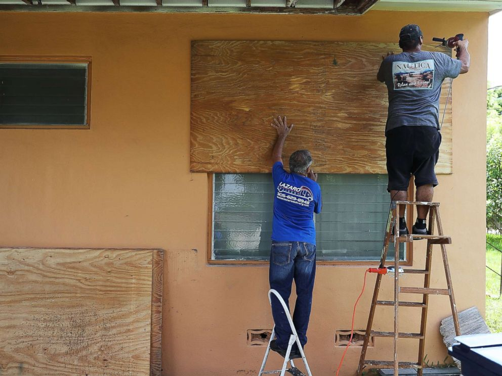 PHOTO: People put up shutters as they prepare a family members house for Hurricane Irma, Sept. 6, 2017, in Miami.